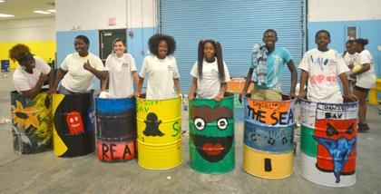 Photo of a group of teens standing in the barrels they just painted