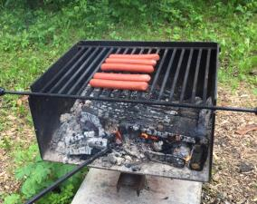 Hot dogs cooking on the fire at Wasagaming Campground, Manitoba