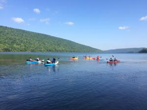 Several kayakers set out on Canadice Lake on a sunny day.