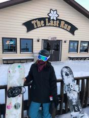 Snowboarder standing outside of ski-up tavern