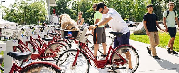 Man with his dog renting a bike at Boulder B Cycle