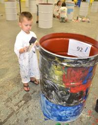 Photo of a little boy painting a barrel
