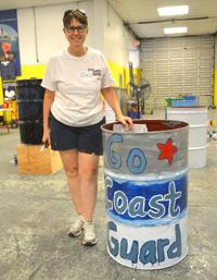Photo of women with U.S. Coast Guard painted barrel