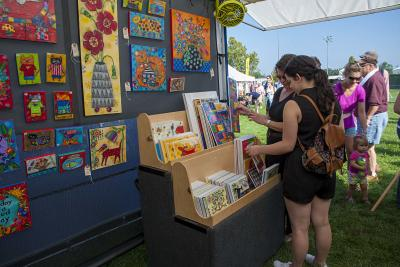 Women examining art at UA Labor Day Arts Festival outdoors
