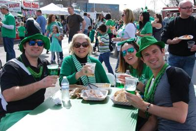 Group of Blarney Bash attendees enjoying food trucks and green beer.