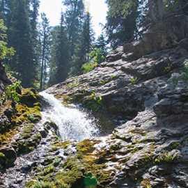 Hikers duck into the grotto under Donut Falls, photo by John Badila