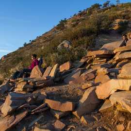 Hikers relax on stone furniture, photo by John Badila