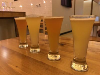 Flight of four different beers on table in minimalist, modern Random Precision taproom
