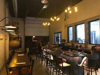 People sitting at bar in Pretentious Brewing's industrial, modern taproom