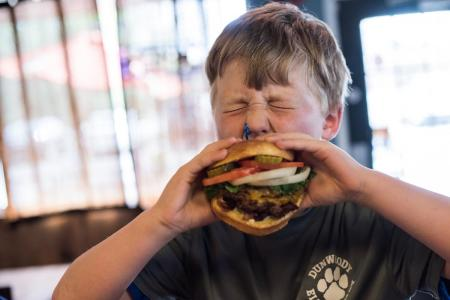Boy taking huge bite at Village Burger