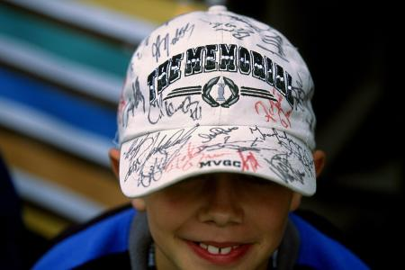 Kid at the Memorial Tournament showing off his hat signed by pro golfers.