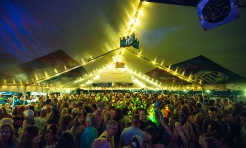 Horseshoe Inn crowd at night under tent