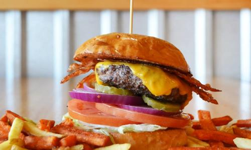 Juicy Burgers & More Stacked burger on plate with fries