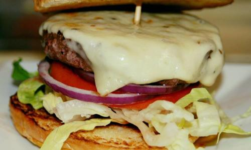 Juicy Burgers & More Burger closeup of cheeseburger on plate