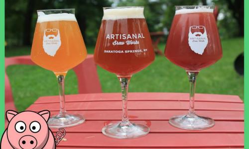 Artisinal Brew Works beers on picnic table with pig graphic