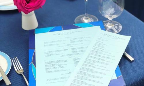 The Blue Hen menu on plate with pink roses