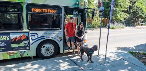 Couple and dog getting off of the Park to Park Hiker Shuttle Chautauqua