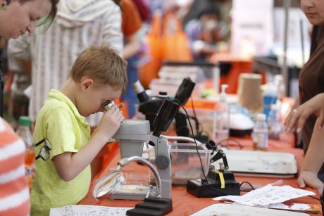 Boy looks through microscope at Imagine RIT