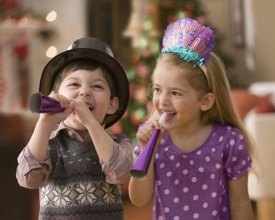 A boy and girl with noisemakers on New Year's Eve.