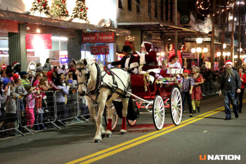 Santa trades his sleigh for a horse-drawn carriage during the Snow on 7th festival each year. (photo by UNation)