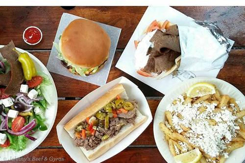 Array of dishes, including hot beef sandwich, gyros sandwich, cheese-covered fries, hamburger and greek salad