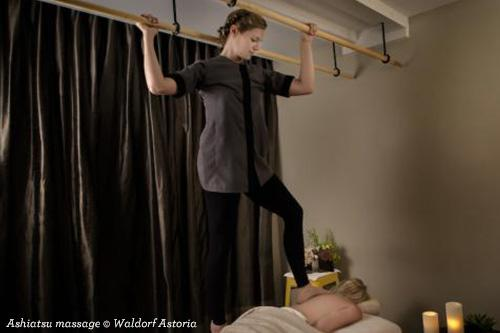 Ashiatsu massage practitioner walking on client