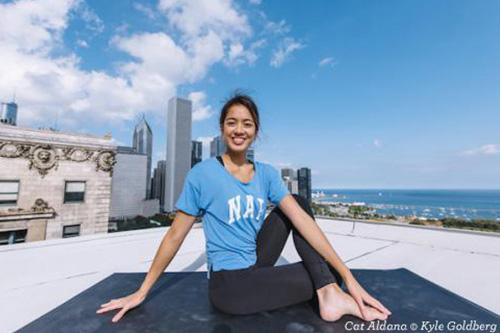 Cat Aldana doing yoga pose on a rooftop