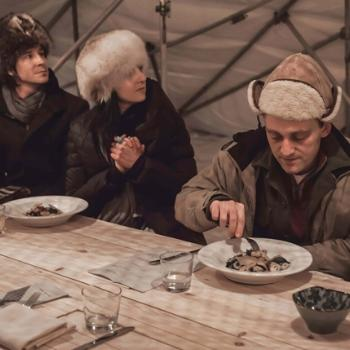 Three people in fur hats sitting at a wood table, about to eat