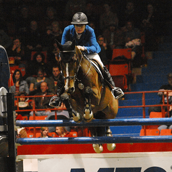 Horse and rider jumping over a vertical jump in front of a full crowd