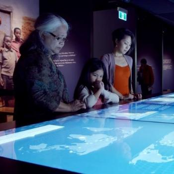 Three people look down at a large touch screen showing an interactive map