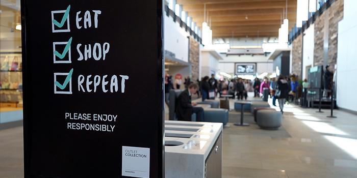 "Sign reading ""Eat. Shop. Repeat."" at OC Winnipeg Outlet Mall"