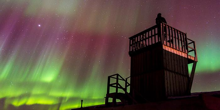 A person observes the northern lights from a wooden observation tower at a Churchill Wild lodge