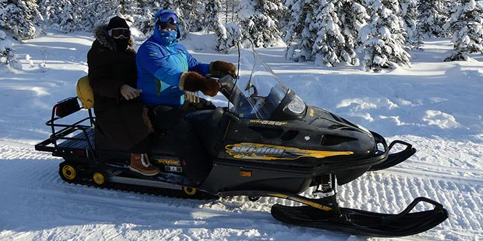 Two people on a snowmobile in the sunshine