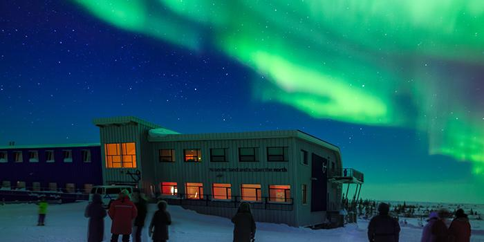 Green northern lights stream across the night sky over a lit building, the Churchill Northern Studies Centre
