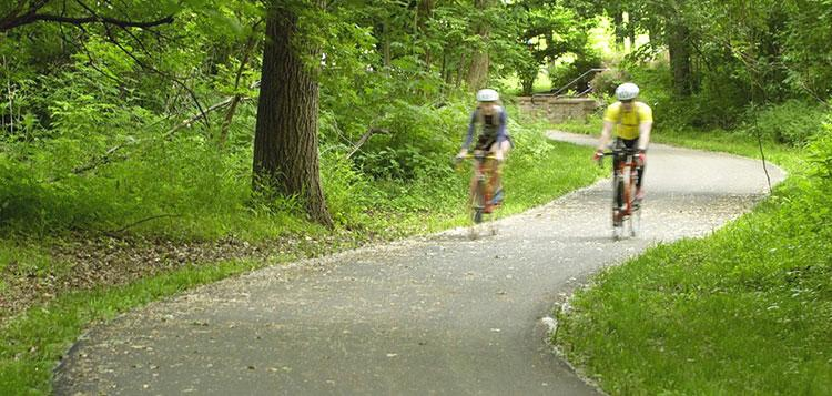 Two bicyclists on the Indian Creek Bike Trail in Overland Park