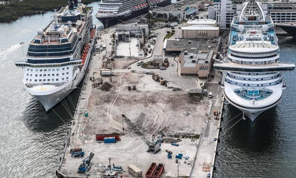 Aerial photo looking south of the Cruise Terminal 25 construction area showing several building walls have been torn down and land has been leveled for new construction.