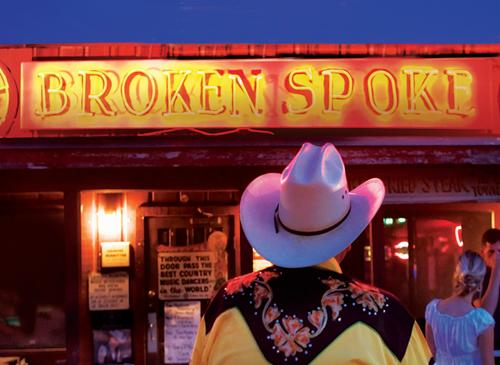 Exterior neon sign at night for iconic dancehall Broken Spoke in Austin Texas