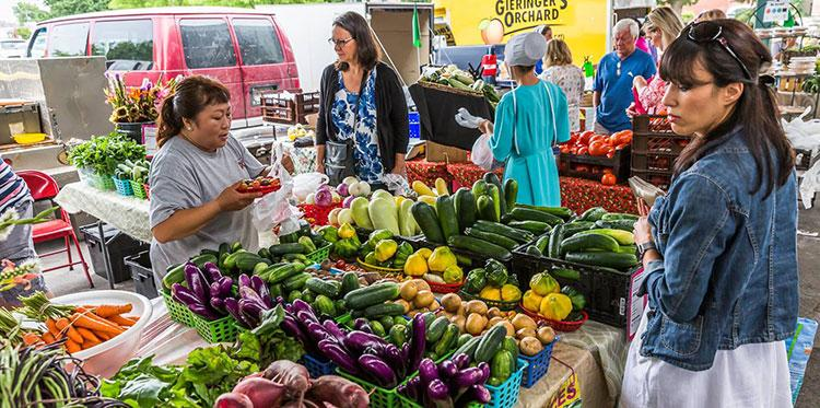 Shoppers examine vegetables at the Open Air Farmers Market in Overland Park