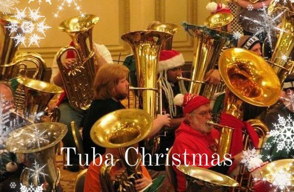 A group of only tuba players dressed in Christmas clothes and playing Christmas