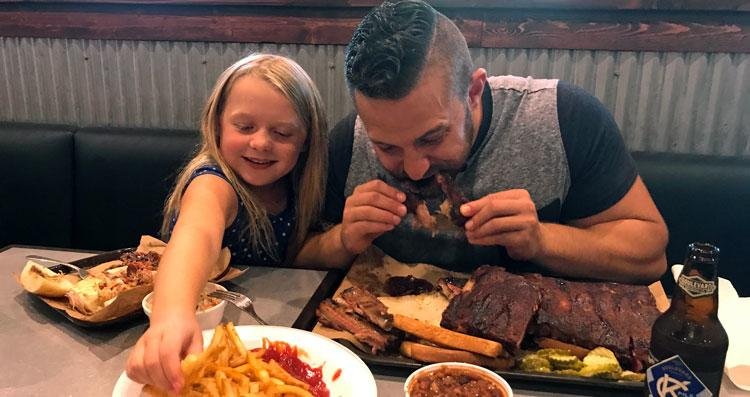 Father and daughter enjoy Joe's KC Ribs and BBQ