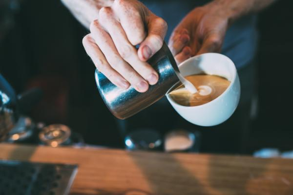 Barista pours milk for cappuccino at The Brew and Brew