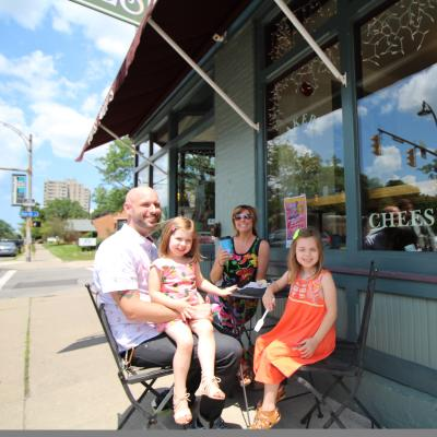 Family sits outside cheesecake shop in Rochester's South Wedge Neighborhood