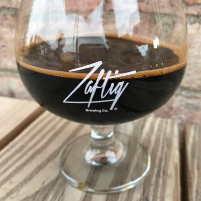 Dark beer in snifter glass printed with Zaftig Brewing logo