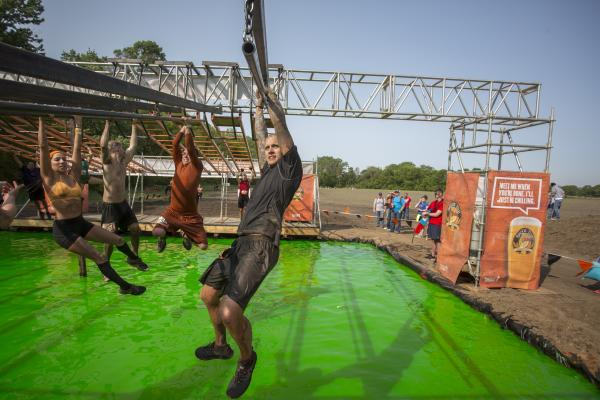 tough mudder participant on Funky Monkey obstacle