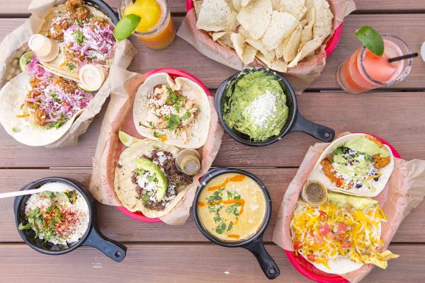 Table spread at Torchy's including tacos, chips, guacamole and queso