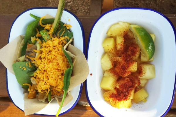 Taco Heads' veggie breakfast enchilada with eggs and cheese, and a side of pineapple with chile and lime