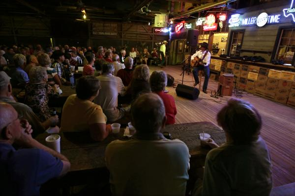 Performer with guitar on stage at Gruene Hall