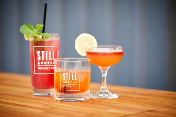 Mixed drinks with Still Austin Whiskey Co logo on glasses