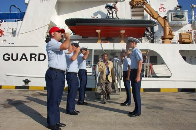 Coast Guard members saluting next to USS Diligence