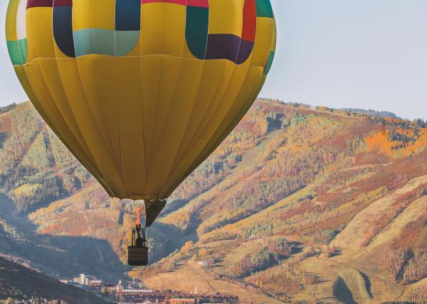 Yellow Hot Air Balloon floating over Park City among mountain scenery
